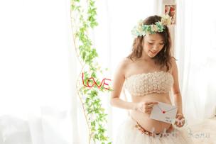 マタニティフォトの時期に関する記事のアイキャッチ画像。手紙を持った妊婦さんがうつむいている様子。花かんむりをかぶって撮影したマタニティフォト。バックのグリーンがとてもきれい。中にはLOVEという文字がある。