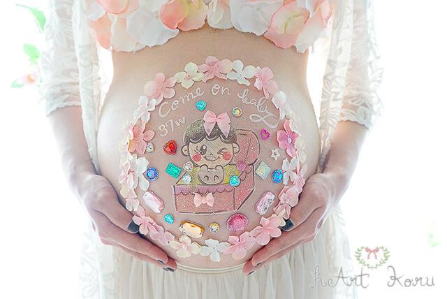 おしゃれで可愛いベリーペイント、マタニティペイントのデザイン。赤ちゃんのイラストがとても可愛い。宝石がたくさん入ってる宝箱から赤ちゃんが元気よく飛び出してくるイラストのデザイン。宝箱の周りはピンクのお花が覆っている。