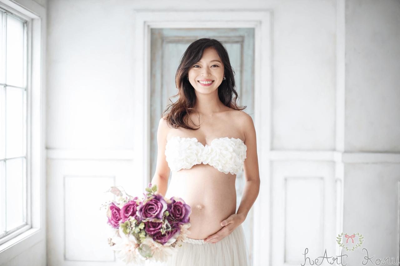 マタニティフォト の画像。紫の花束を持ってこちらを向いた美人の妊婦さん。