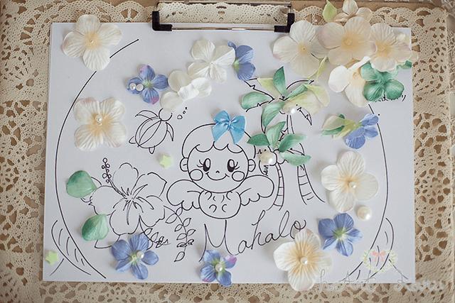 A4の紙の上にベリーペイントの下書きのデザインが描かれている。シンプルなデザイン。紫と白の色とりどりの花に囲まれた赤ちゃんキャラクター。この下書きを元にベリーペイントのデザインが描かれていく。