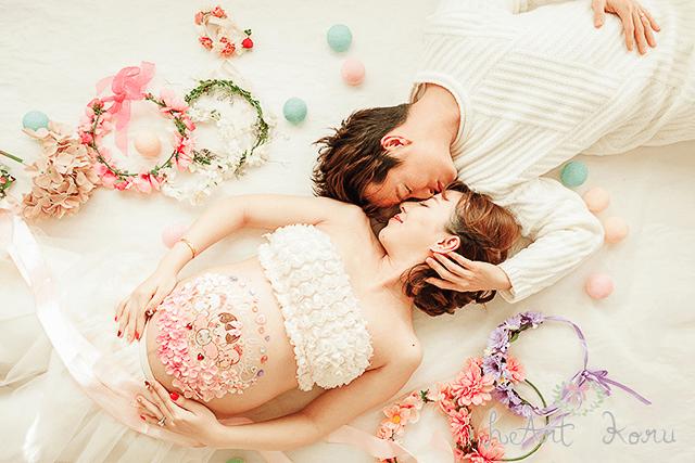 おしゃれで可愛いベリーペイント。見つめ合う夫婦を撮影したマタニティフォト。ピンクを基調としたベリーペイントになっていている。