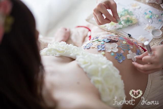 白と青の花のベリーペイントをペイントしている様子。妊婦さんがペイントの様子に釘ずけになっている写真。