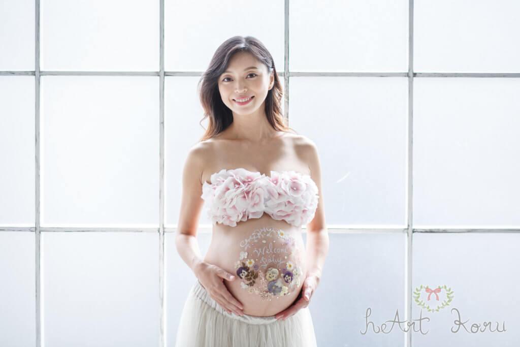 シンプルで可愛いベリーペイント。押し花を使ってデザインになっている。クールなスタジオで撮影されたマタニティフォトの写真。モデルの女性がこちらをみて微笑んでいる。