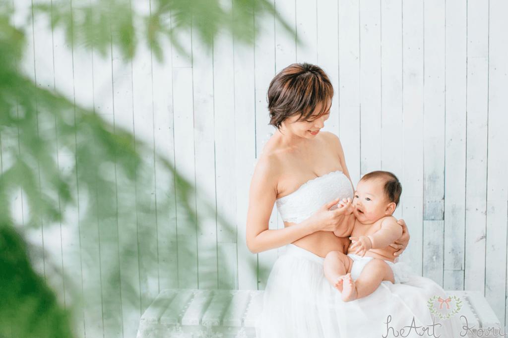 授乳フォトの写真。赤ちゃんが笑顔でお母さんの方を向いている。